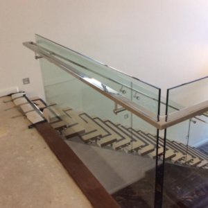 Internal glass balustrading face fixed to timber stair treads with a 50x25mm offset stainless steel polished handrail